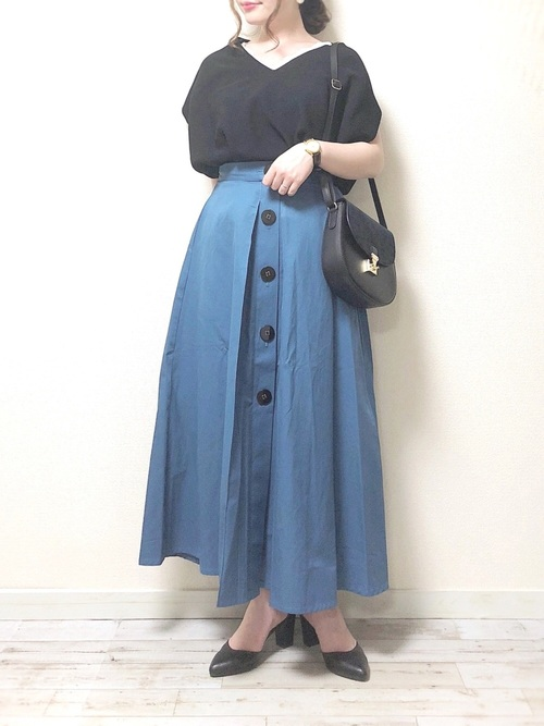 黒コットンコクーンVプルオーバーとブルーフロントボタンロングフレアスカートに黒パンプスを履いた女性