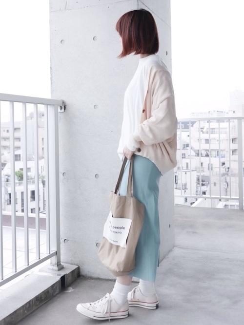 白ドルマンリブニットカーディガンとブルーシェルタリングオックススカートにベージュトートバッグを合わせた女性