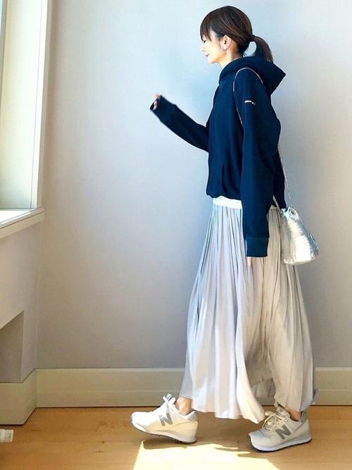 紺パーカーとグレーサテンロングスカーフスカートにシルバー巾着ショルダーバッグを合わせた女性