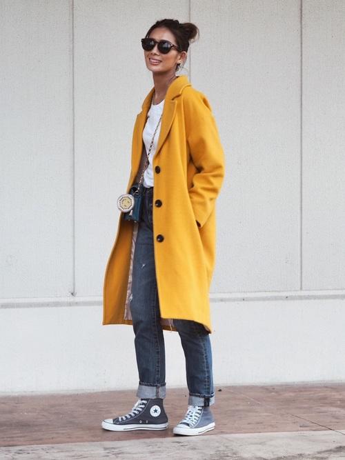 黄色チェスターロングコートと白Tシャツにデニムストレートパンツを履いた女性
