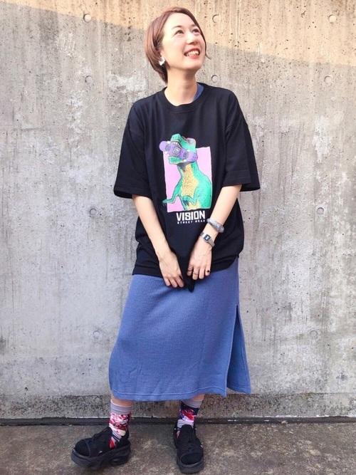 黒プリントTシャツと青ワッフルカットワンピースに黒エアマックスココを履いた女性