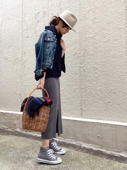 デニムジャケットと紺パーカーにグレーリブニットタイトスカートを履いた女性