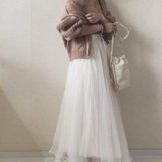 ゆるっと羽織ったベージュのカーディガンに白のフレアスカートが軽やかな秋コーデ