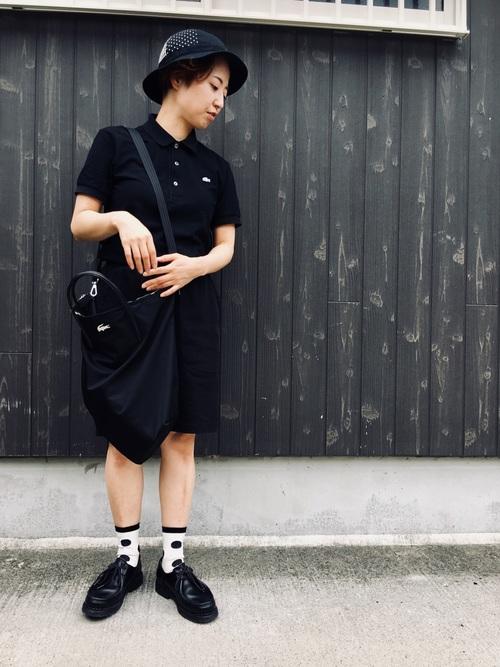黒ラコステポロシャツワンピースと黒ショルダーバッグに黒ローファーを履いた女性