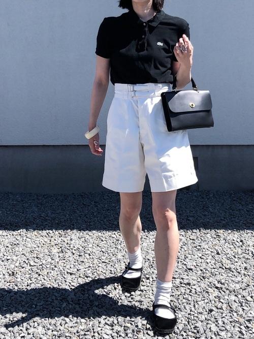 黒ラコステポロシャツと白ハーフパンツに黒ハンドバッグを合わせた女性