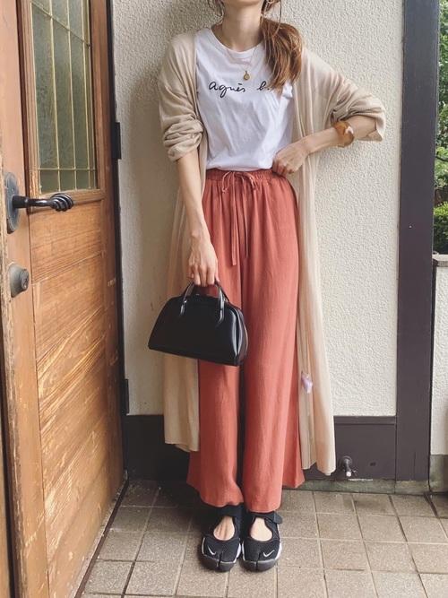黒スニーカーとベージュロングカーディガンにオレンジワイドパンツを履いた女性