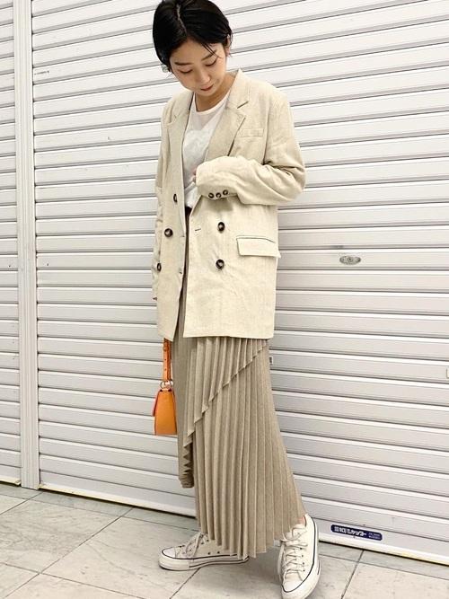 白スニーカーとベージュテーラードジャケットにベージュプリーツスカートを履いた女性
