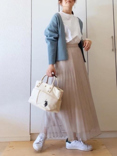 白スニーカーとグリーンカーディガンにベージュシアープリーツスカートを履いた女性