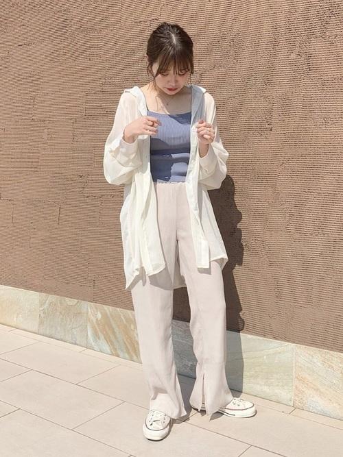 白スニーカーと白ーシアーシャツに青タンクトップを着た女性