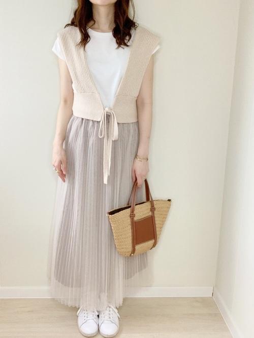 白スニーカーとベージュニットベストにチュールプリーツスカートを履いた女性