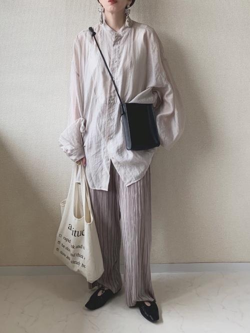 ニュアンスカラーオーバーサイズシャツとライトグレープリーツパンツにスクエアシンプルショルダー黒バッグを合わせた女性
