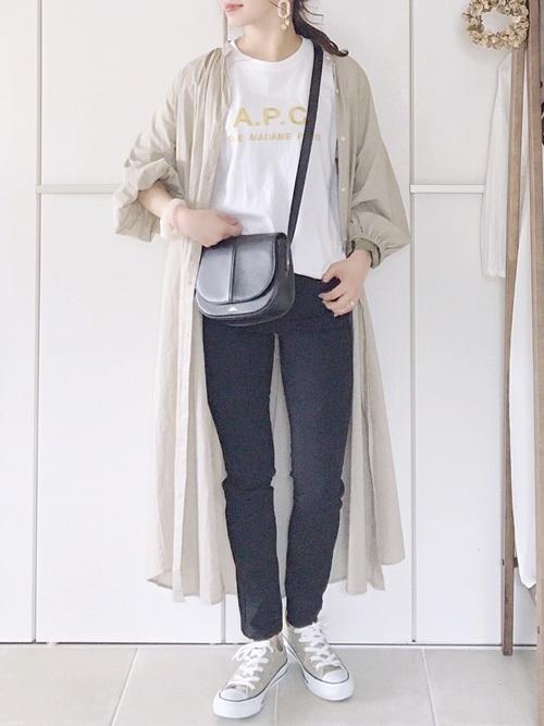 刺繍ロゴTシャツとベージュギャザーシャツワンピースにショルダーフラップ黒バッグを合わせた女性