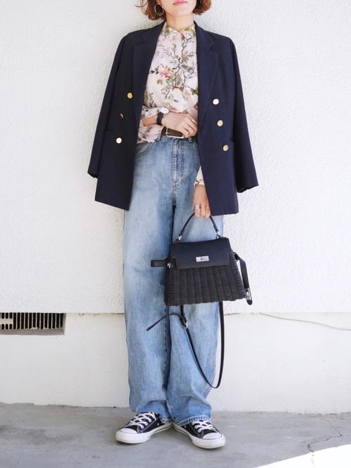 ベージュ花柄シャツとネイビーテーラードジャケットにレザーコンビかごハンド黒バッグを合わせた女性