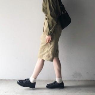 カーキスリーピング古着シャツとウエストベルトベージュハーフパンツにブラックレースアップドレスシューズを履いた女性
