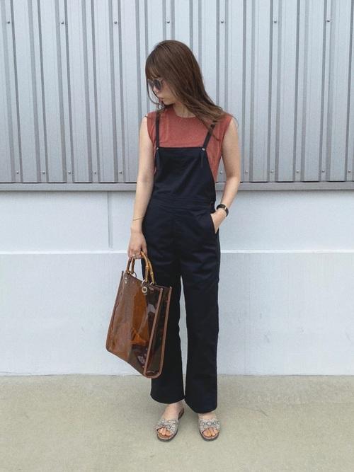 ブラウンTシャツと黒サロペットにクリアトートバッグを合わせた女性