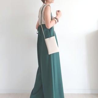 ベージュタンクトップと緑バックリボンサロペットに白ミニバッグを合わせた女性