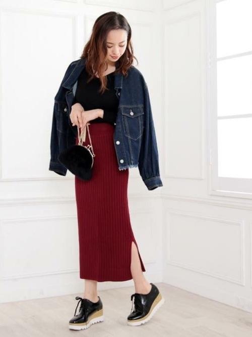 デニムジャケットとワインレッドリブニットスカートに黒がま口ミニバッグを合わせた女性