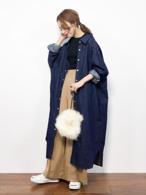 ロングデニムシャツワンピースとベージュワイドパンツにファーバッグを合わせた女性