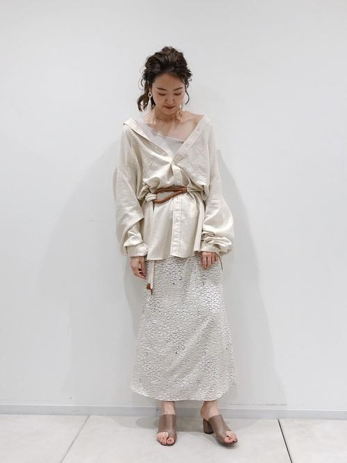ロング白デニムシャツとウエストマークベルトにマーメイドスカートを履いた女性