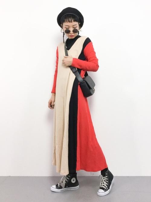 ロデオクラウンズのオレンジパレット切り替えマキシワンピースと黒スニーカーに黒ハンチング帽を合わせた女性