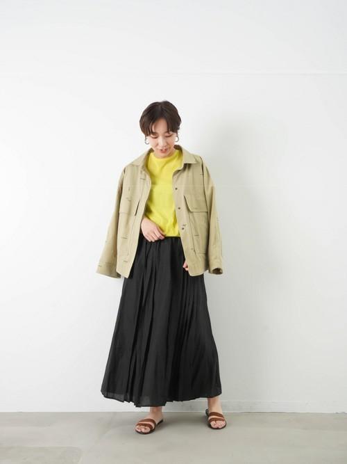 黒リネンプリーツスカートとベージュサファリジャケットにイエローカットソーを合わせた女性