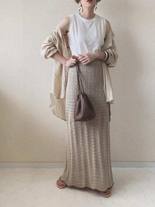 ベージュフレンチリネンCPOシャツと白ベーシックタンクトップにベージュレイシーニットスカートを履いた女性