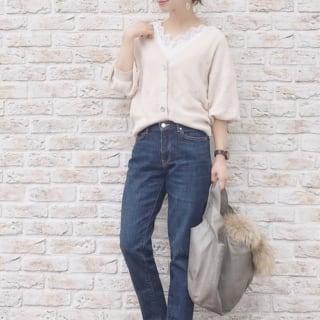 白レースリブカットソーとショート丈白カーディガンにテーパードデニムパンツを履いた女性