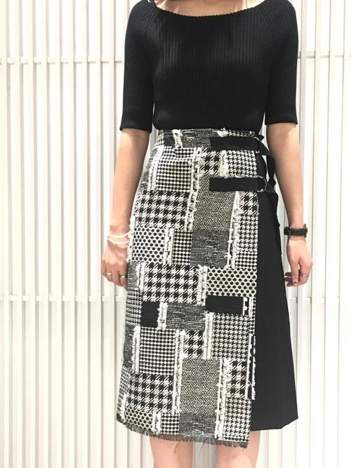 タイトニットと千鳥柄ジャガードラップスカートにシルバーアクセサリーを合わせた女性