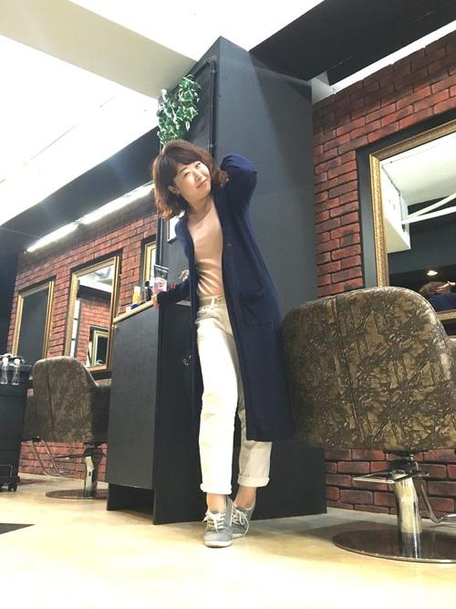 ピンクカットソーとブルーロングカーディガンにロールアップホワイトデニムパンツを履いた女性