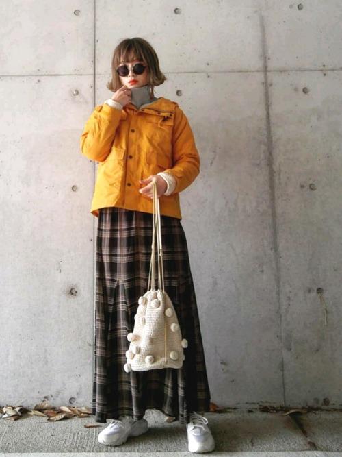 イエローボアライナー付きマウンテンパーカーとサイドスリットハイネック裏毛スウェットにチェックフレアロングスカートを履いた女性