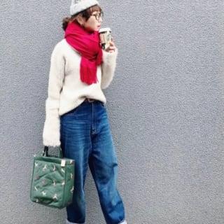 白のセーターに大判赤ストールを巻いた女性