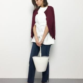 ボルドークルーネックカーディガンとフレアチュニックにスリットストレートデニムパンツを履いた女性