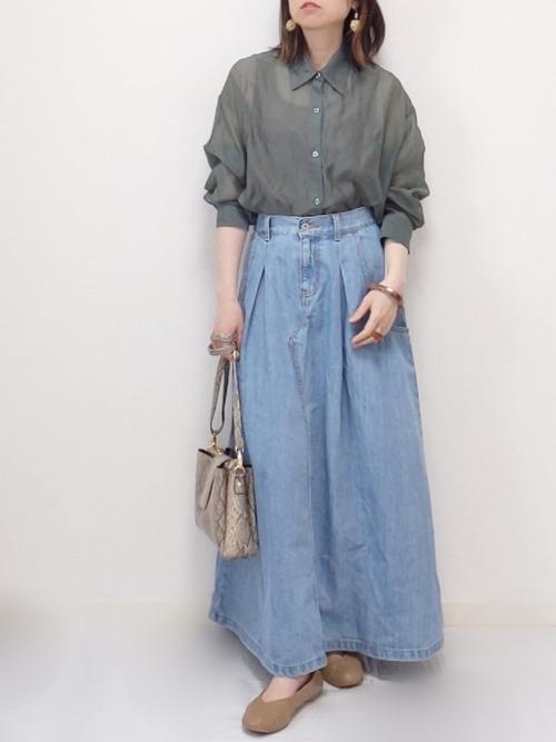 カーキシアーシャツとフレアロングデニムスカートにベージュバレエシューズを履いた女性