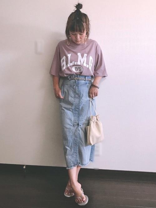 ダスティピンクTシャツとライトブルーロングタイトデニムスカートにビーチサンダルを履いた女性