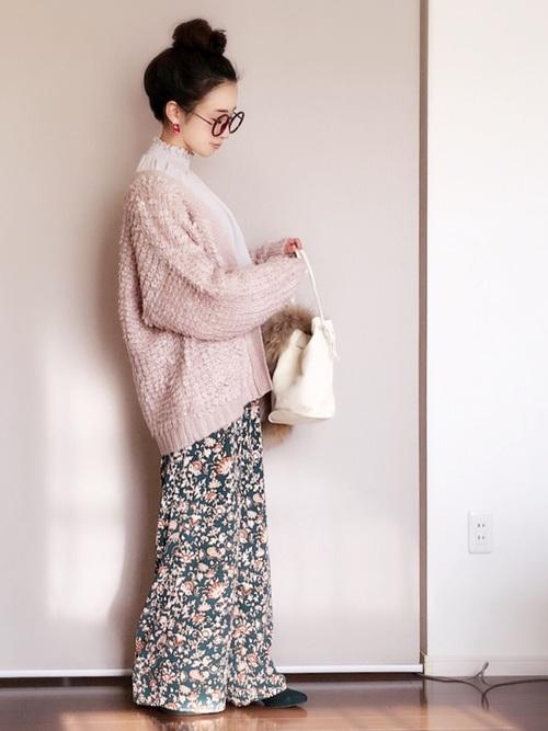 グリーン花柄ワイドイージーズボンにピンクカーディガンを着た女性