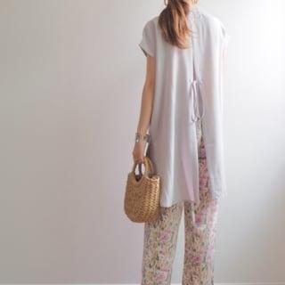 ベージュ花柄リラックスズボンにトロピカルバックスリットシャツを着た女性