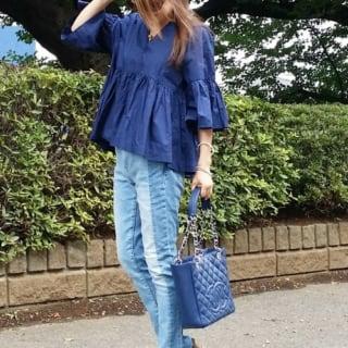 ブルーシャツブラウスとデニムパンツにシャネルのショルダーバッグを合わせた女性