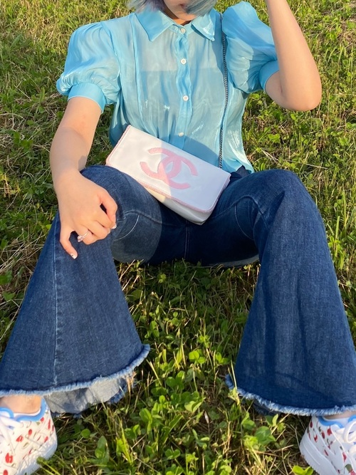 ブルーサテンブラウスとデニムベルボトムパンツにシャネルのチェーンバッグを合わせた女性