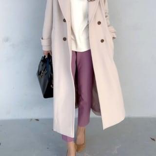 アイボリーチェスターコートとピンクテーパードパンツにサンローラントートバッグを合わせた女性