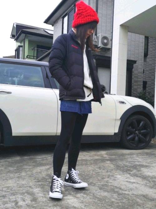 ブラックダウンジャケットにデニムミニスカートを履いた女性