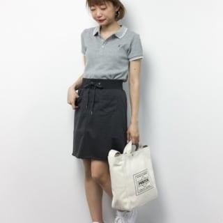 グレーカノコラインポロシャツと黒フロントポケットカットミニスカートに白ローカットスニーカーを履いた女性