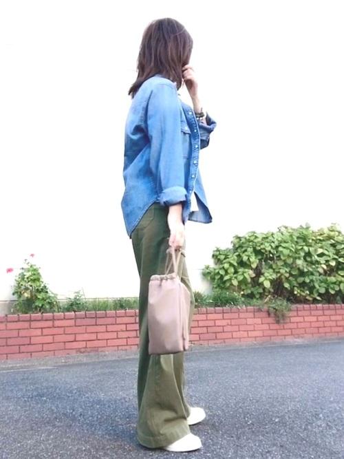 ブルーデニムシャツとカーキワイドパンツに白スニーカーを履いた女性