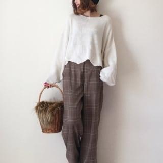 ボリューム袖ホワイトニットとチェック柄ワイドパンツにホワイトスニーカーを履いた女性
