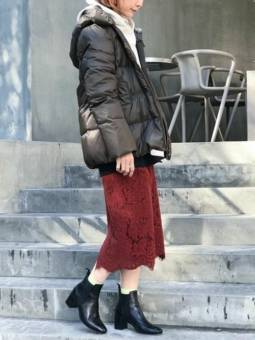 ナノユニバースのダウンコートとレーシィタイトスカートとショートブーツのコーデの女性