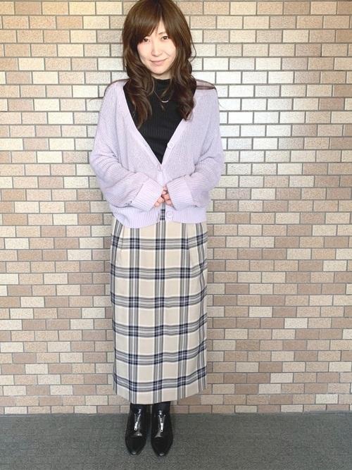 パープルニットカーディガンとベージュタータンチェックタイトスカートと黒マニッシュヒールシューズのコーデの女性