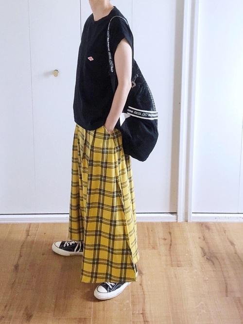 黒ノースリーブTシャツとイエロータータンチェックロングフレアスカートと黒リュックのコーデの女性