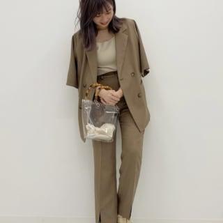 ブラウンスーツとクリアバッグとゴールドサンダルのコーデの女性