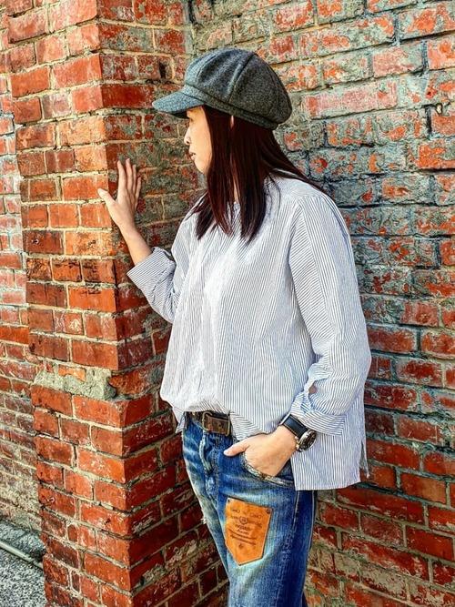 ピンストライプシャツとディースクエアードダメージジーンズにグレーキャスケットを合わせた女性