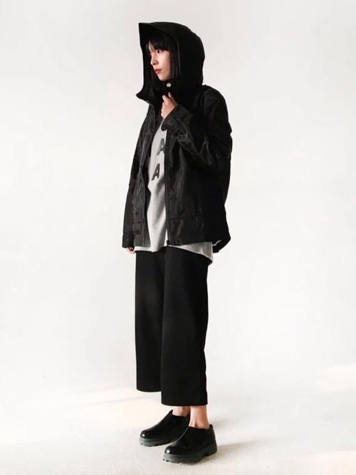 ディースクエアードフードジャケットとグレーロゴセーターに黒ワイドパンツを履いた女性