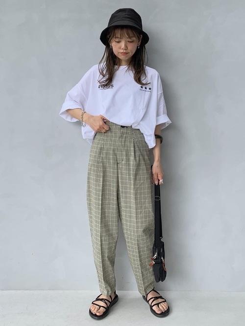 バケットハットとビッグTシャツにチェックテーパードパンツを履いた女性